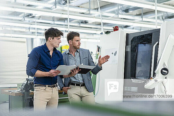 Businessman explaining male engineer with file document about manufacturing in factory