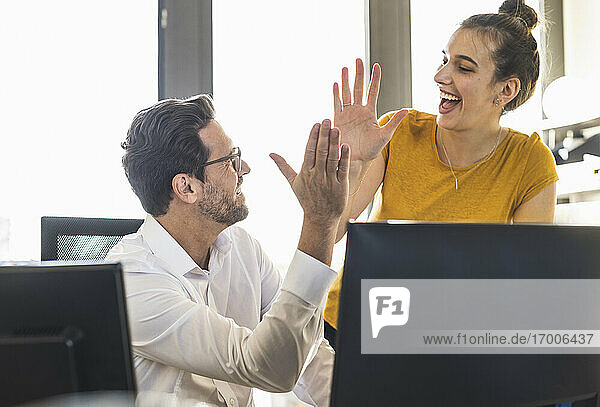 Business people giving high five while working together st office