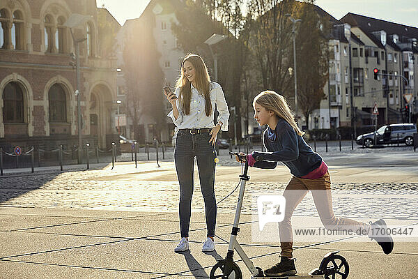 Girl riding push scooter on footpath with mother standing in background at city