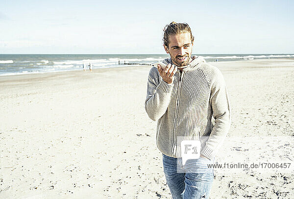 Man with hand in pocket talking on mobile phone while walking at beach during sunny day