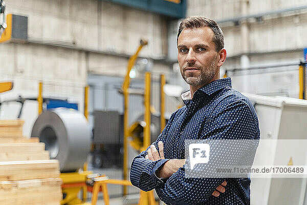 Confident businessman with arms crossed standing at industry