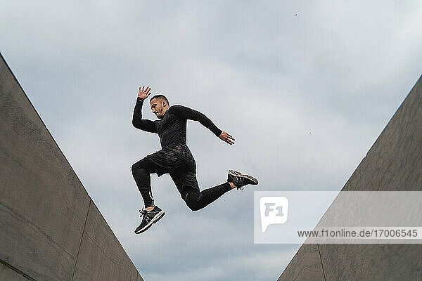 Athlete jumping on wall against sky
