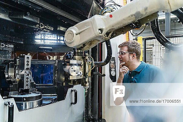 Thoughtful male worker analyzing while standing at factory