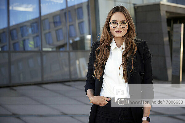 Businesswoman with hands in pockets standing on footpath