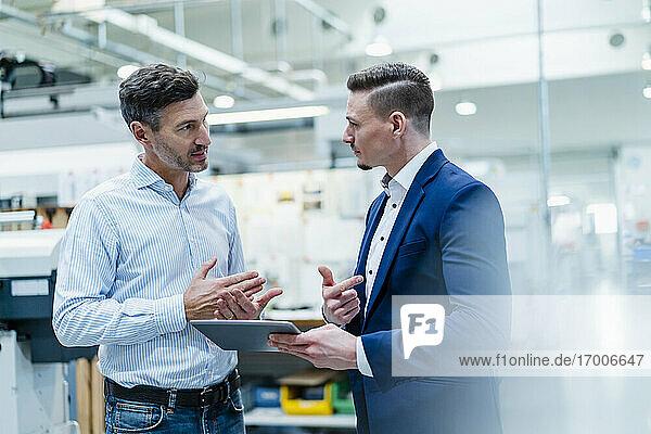 Männliche Fachkräfte mit digitalem Tablet im Gespräch in einer Fabrik stehend