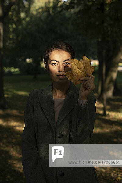 Female entrepreneur holding dry leaf while standing in park during autumn