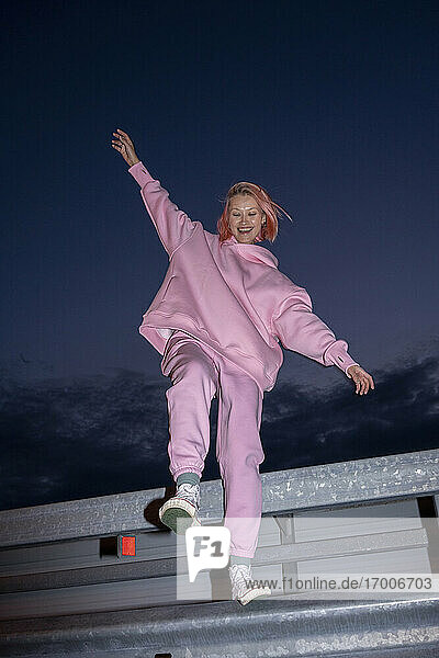 Young woman with pink hair wearing pink track suit standing on one leg on road barrier at night