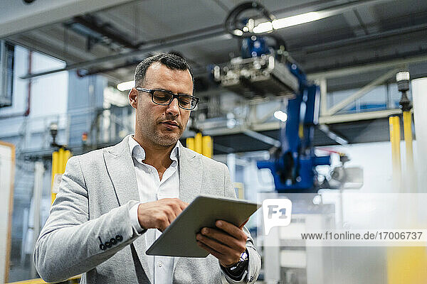 Mature businessman wearing eyeglasses working on digital tablet in industry