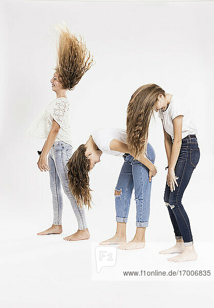 Playful siblings tossing hair against white background