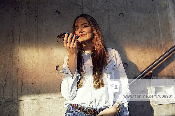 Young businesswoman with hands in pockets talking on mobile phone while standing against wall