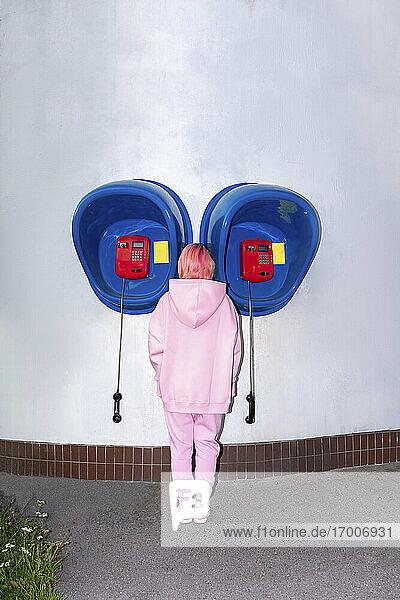 Rückansicht einer jungen Frau mit rosa Haaren und rosa Kapuzenshirt  die vor einer Telefonzelle steht Rückansicht einer jungen Frau mit rosa Haaren und rosa Kapuzenshirt, die vor einer Telefonzelle steht