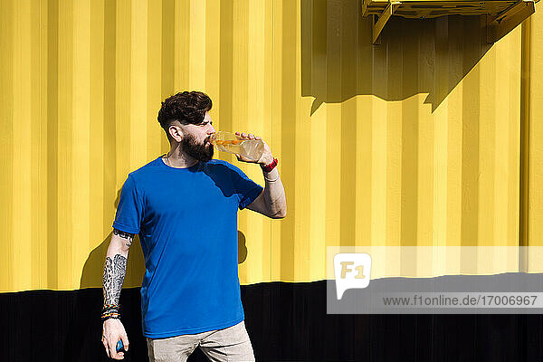 Young man with tattoo standing in front of yellow wall  drinking water from a bottle