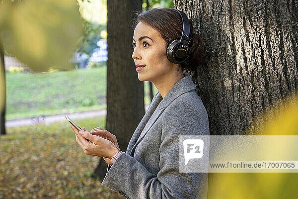 Weibliche Unternehmerin  die im Herbst im Park mit ihrem Smartphone Musik hört und darüber nachdenkt Weibliche Unternehmerin, die im Herbst im Park mit ihrem Smartphone Musik hört und darüber nachdenkt