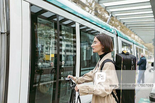 Frau mit Instrumentenkoffer und Elektroroller an der Straßenbahn in der Stadt Frau mit Instrumentenkoffer und Elektroroller an der Straßenbahn in der Stadt