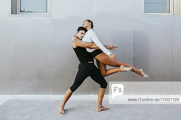 Young professional acrobats embracing each other while dancing against wall