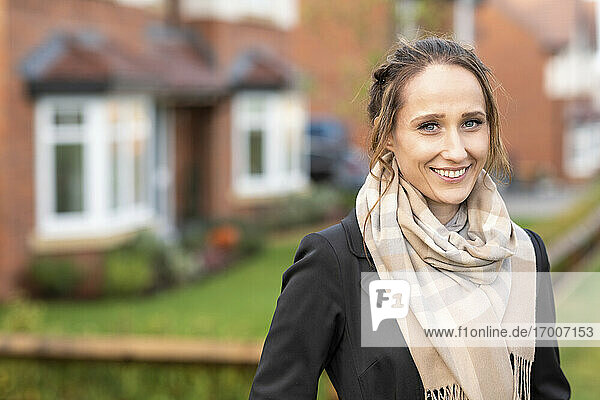 Smiling young woman in scarf standing outside new home