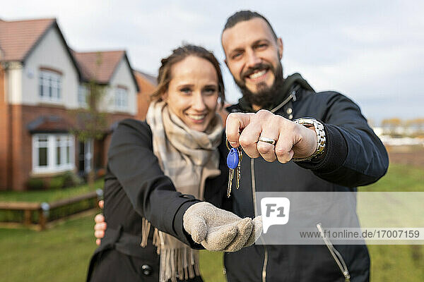 Happy man giving keys of new house to girlfriend while standing in front yard