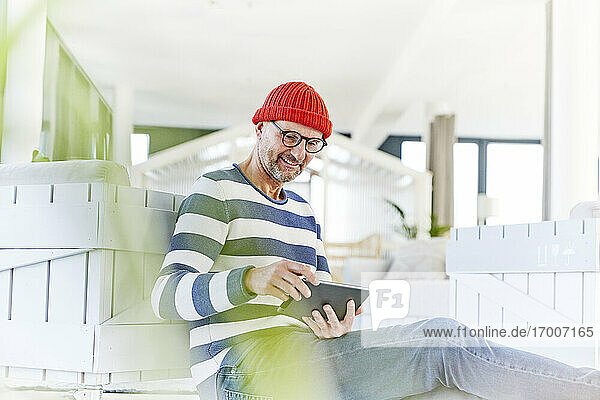 Smiling man wearing knit hat and eyeglasses using digital table while sitting at home