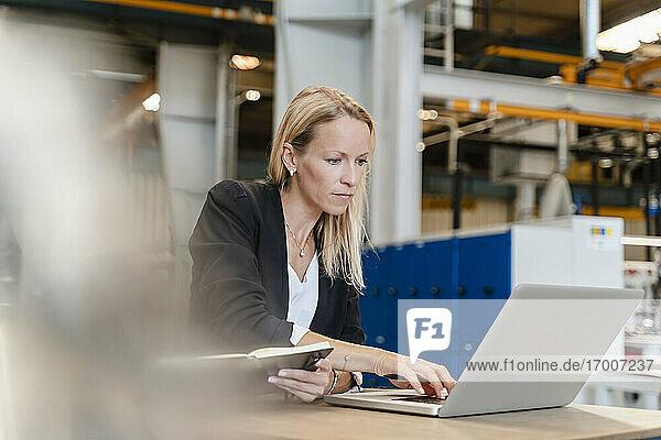 Unternehmerin arbeitet am Laptop  während sie in einer Fabrik sitzt