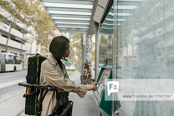 Frau mit Instrumentenkoffer  die einen Fahrkartenautomaten benutzt  während sie mit einem Elektroroller an einer Straßenbahnhaltestelle in der Stadt steht Frau mit Instrumentenkoffer, die einen Fahrkartenautomaten benutzt, während sie mit einem Elektroroller an einer Straßenbahnhaltestelle in der Stadt steht
