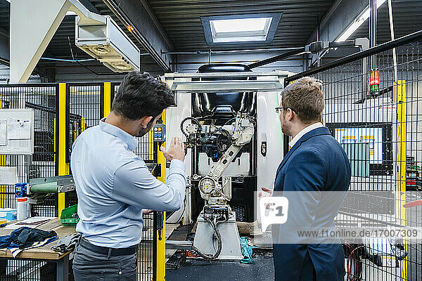 Businessman explaining male colleague about machinery in industrial factory