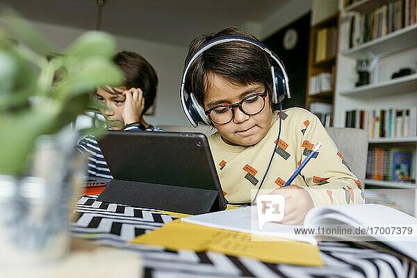 Junge  der mit einem männlichen Freund beim E-Learning zu Hause sitzt und über ein digitales Tablet Notizen schreibt Junge, der mit einem männlichen Freund beim E-Learning zu Hause sitzt und über ein digitales Tablet Notizen schreibt