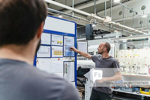Wartungsingenieur  der mit einem Kollegen in einer Fabrik über einen Geschäftsplan diskutiert