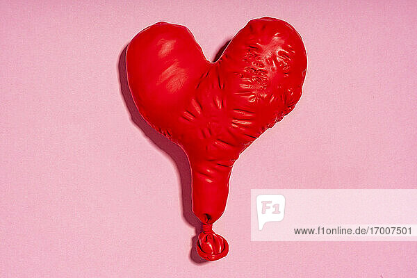 Studio shot of red heart shaped deflated balloon