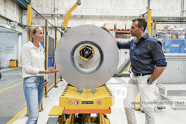 Female entrepreneur discussing about steel roll with male colleague while standing in factory