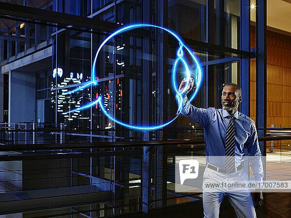 Männlicher Ophthalmologe  der einen Augapfel im Labor eines Krankenhauses mit Licht bemalt Männlicher Ophthalmologe, der einen Augapfel im Labor eines Krankenhauses mit Licht bemalt