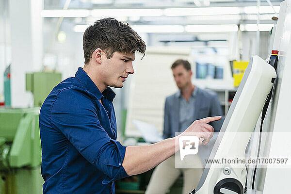 Männlicher Ingenieur bei der Bedienung von Maschinen in einer Fabrik