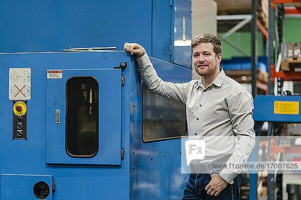 Lächelnder Geschäftsmann mit Hand in der Tasche in einer Fabrik stehend