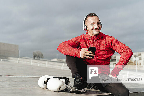 Happy man looking away while using mobile phone sitting outdoors