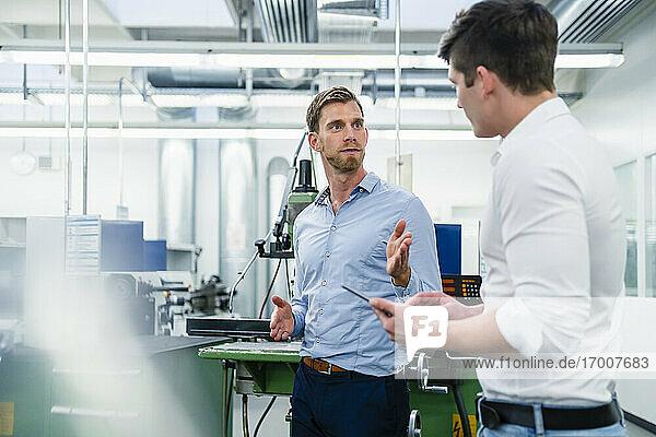 Männlicher Unternehmer  der einem Mitarbeiter bei der Arbeit in der Industrie etwas erklärt