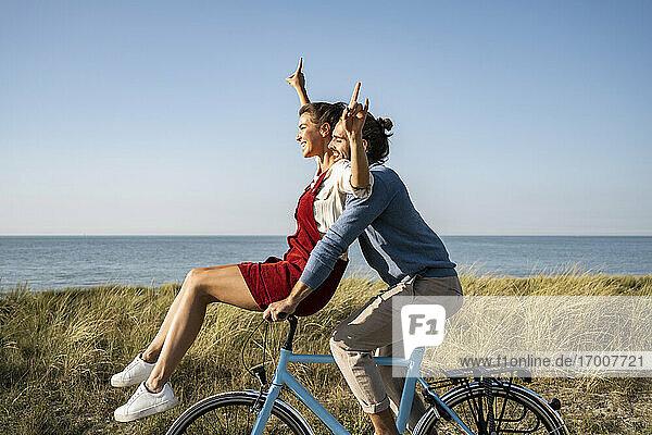 Glückliches Paar bei einer gemeinsamen Fahrradtour gegen den klaren Himmel Glückliches Paar bei einer gemeinsamen Fahrradtour gegen den klaren Himmel