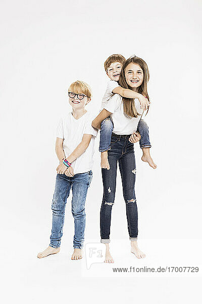 Cheerful siblings in casuals against white background