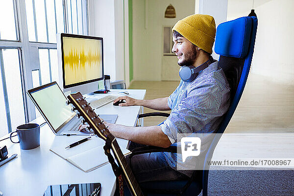 Male expertise using laptop while sitting on chair by guitar at studio