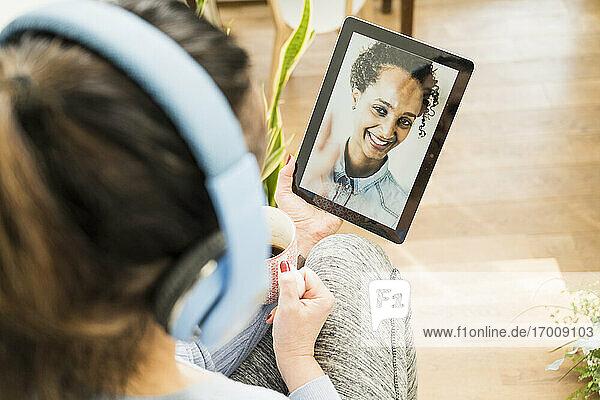 Multiethnische Freundinnen bei einem Videoanruf über ein digitales Tablet zu Hause Multiethnische Freundinnen bei einem Videoanruf über ein digitales Tablet zu Hause