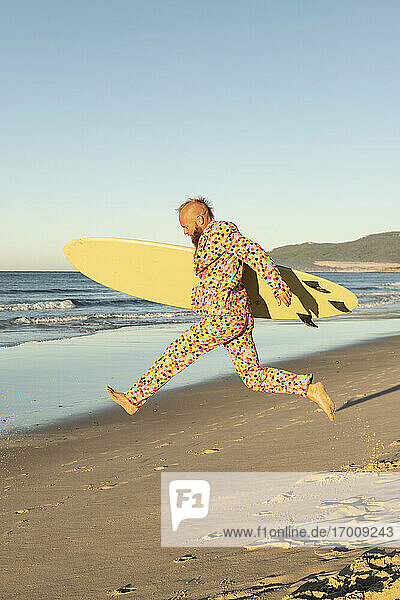 Carefree man running with surfboard on beach