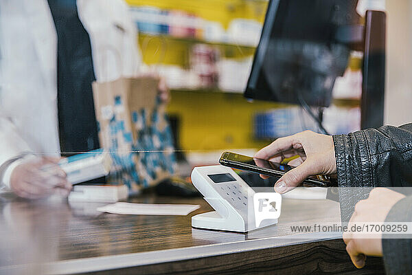 Hand of customer with mobile phone at checkout counter in chemist shop