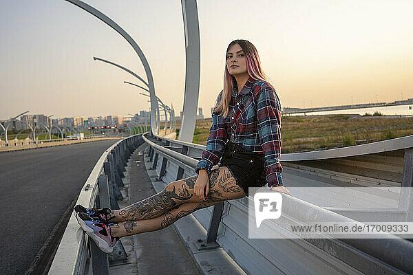 Hipster-Frau mit cooler Einstellung sitzt auf Geländer an Brücke gegen klaren Himmel Hipster-Frau mit cooler Einstellung sitzt auf Geländer an Brücke gegen klaren Himmel