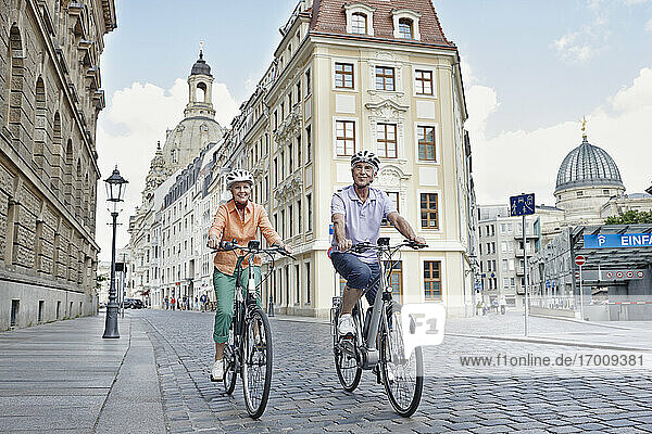 Senior tourists riding electric bicycle against Frauenkirche Cathedral at Dresden  Germany