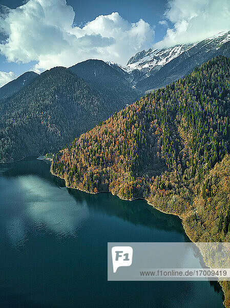 Aerial view of Lake Ritsa surrounded by forested mountains in autumn