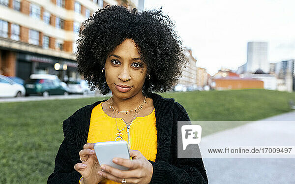 Young woman with afro hair using mobile phone while standing in city