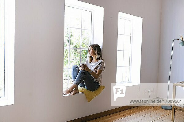 Woman with coffee cup sitting on window sill at home