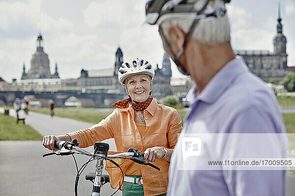 Senior woman with electric bicycle smiling while looking at man while standing at Frauenkirche Cathedral  Dresden  Germany