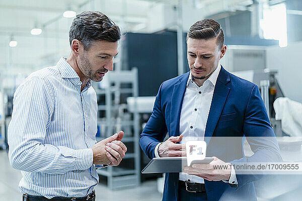 Geschäftsleute arbeiten gemeinsam an einem digitalen Tablet in der Industrie