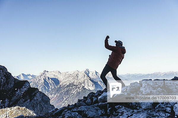Sorgloser reifer Mann tanzt auf einem Berg gegen den klaren Himmel im Winter Sorgloser reifer Mann tanzt auf einem Berg gegen den klaren Himmel im Winter