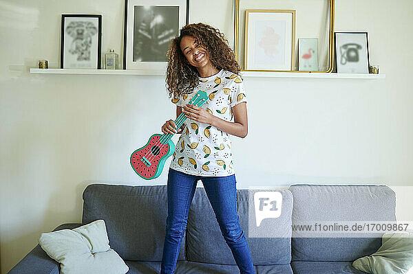Glückliche junge Frau mit lockigem Haar  die eine Ukulele hält  während sie zu Hause auf dem Sofa steht Glückliche junge Frau mit lockigem Haar, die eine Ukulele hält, während sie zu Hause auf dem Sofa steht
