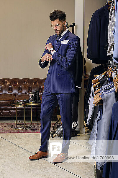 Man in blue pinstripe suit in tailors boutique